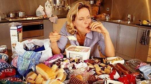 binge eating disorder picture of woman binge eating tons of food in front of her on the table