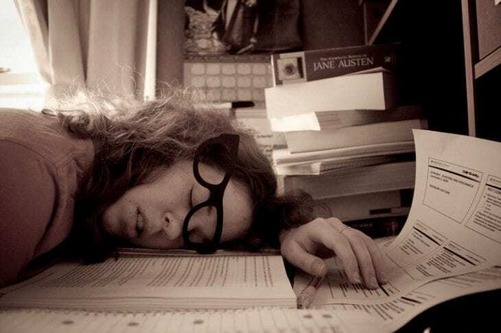 picture of woman sleeping at her desk to show how to avoid things that make you sleepy before bed