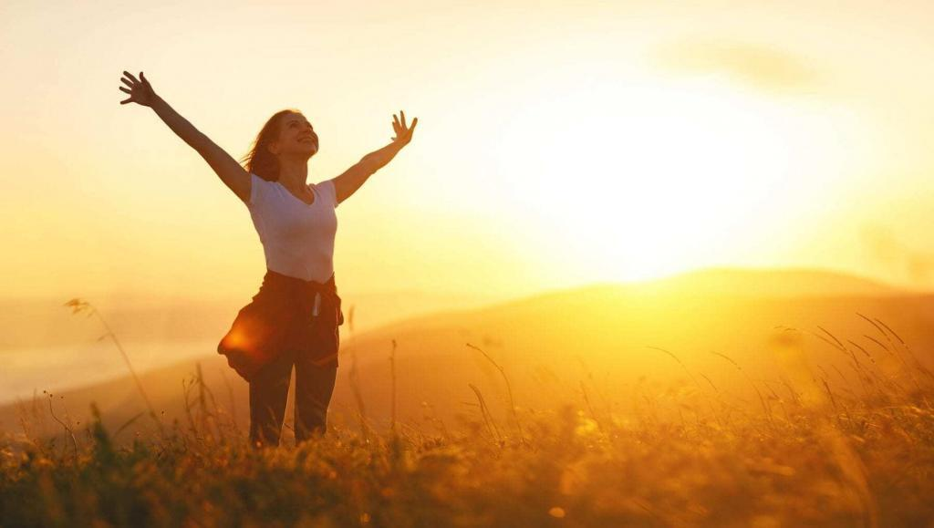 Happy woman on sunset in nature with open hands